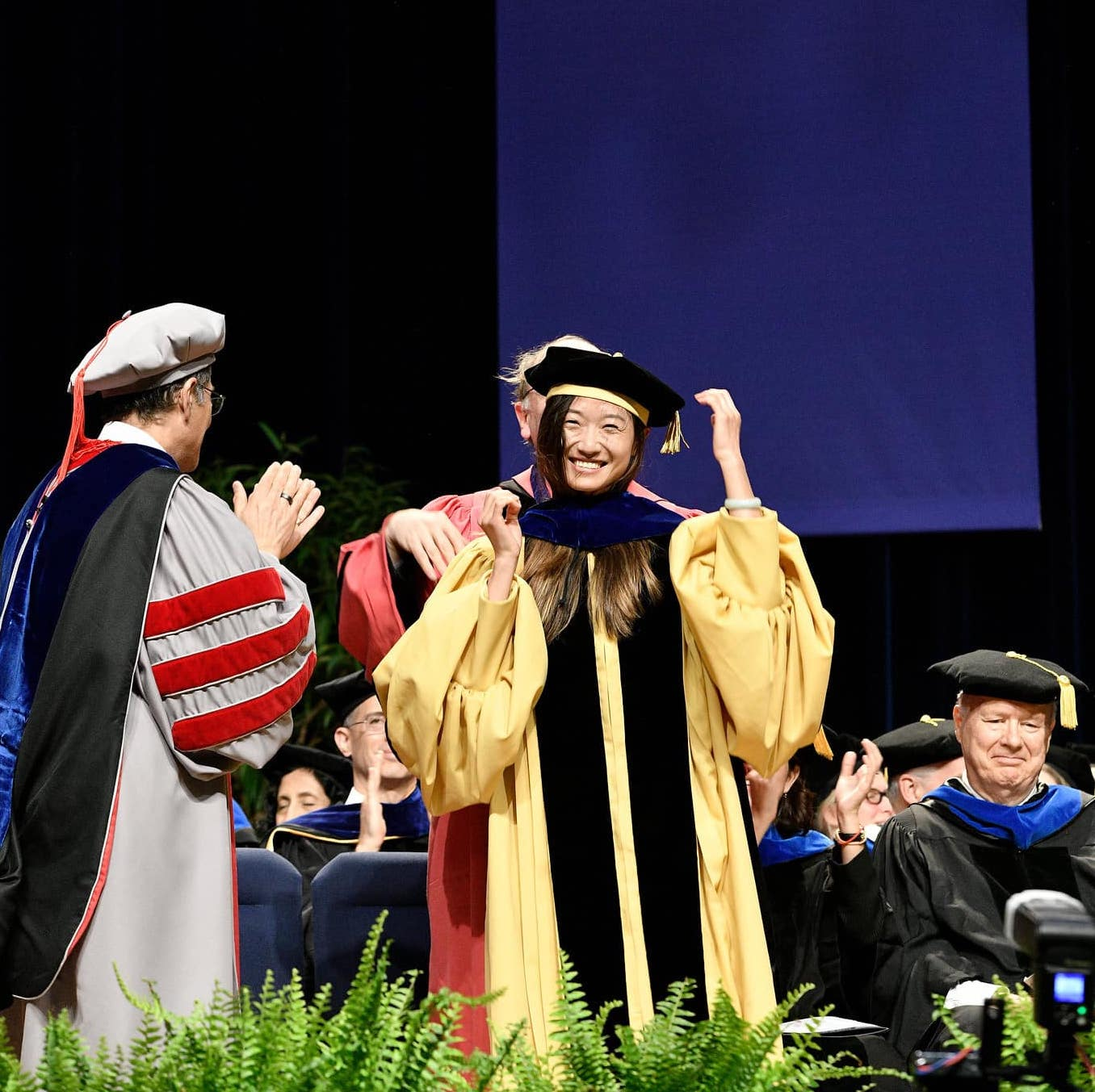 A Johns Hopkins SAIS doctoral candidate receives her robes at commencement