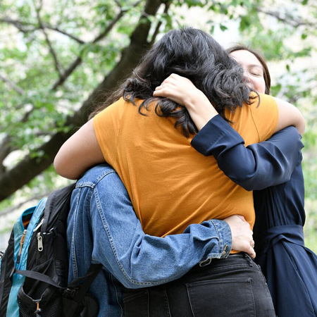 Three Johns Hopkins SAIS alumnae share a hug at a reunion.