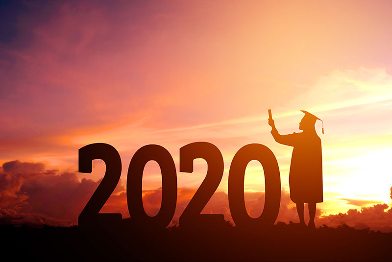 A graduate looking off into the sunset next to a 2020 sign.