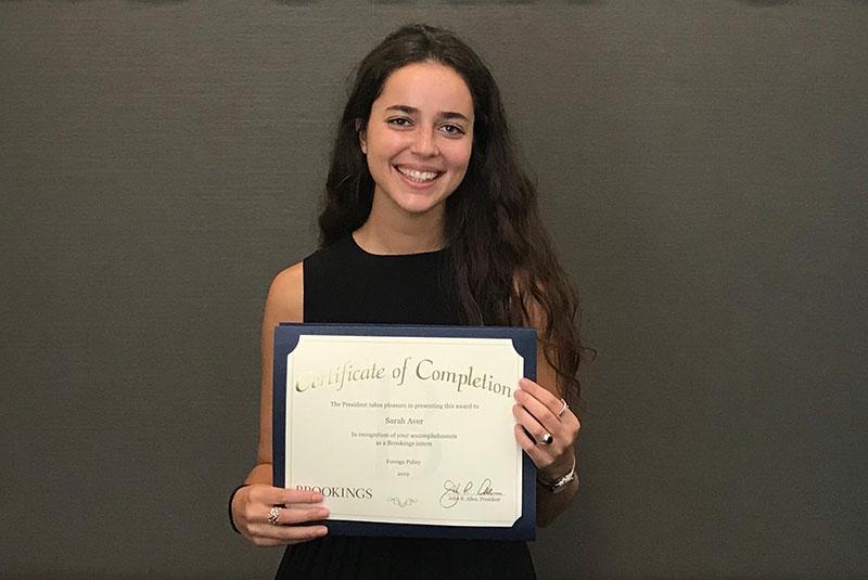 photo of SAIS student holding an award certificate